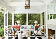 """Captivated by Draper""""s interiors after reading a copy of In the Pink, the owners decided that the porch should evoke the late designer""""s work. Bringing in the blue tones of the nearby pool, a graphic Lee Jofa fabric was used for accent pillows while a Manuel Canovas khaki-and-white material was chosen because of the clients"""" love of stark white prints. Duncan fabricated the Draper-esque mirrored overmantel by applying painted bamboo picture frame molding to a sheet of mirror."""