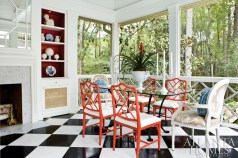"""Duncan matched the black-and-white marble floors""""a Dorothy Draper hallmark""""to those in the foyer of the main residence. The dining chairs"""" crisp white Sunbrella fabric is the perfect foil for the chairs"""" red framing and the built-in bookshelves with red-painted recesses."""