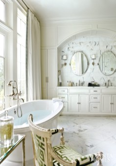 16. Calacatta marble heightens the luxury quotient in this master bathroom designed by Amy D. Morris, while cotton window treatments with trim and an antique chair in a scalamandre velvet add up-to-date energy.