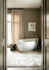 11. Marble floors set the tone for a sumptuous master bath that includes a stand-alone waterworks tub with a kallista tub filler and area rug from Designer Carpets. Interior design by Barbara Westbrook.