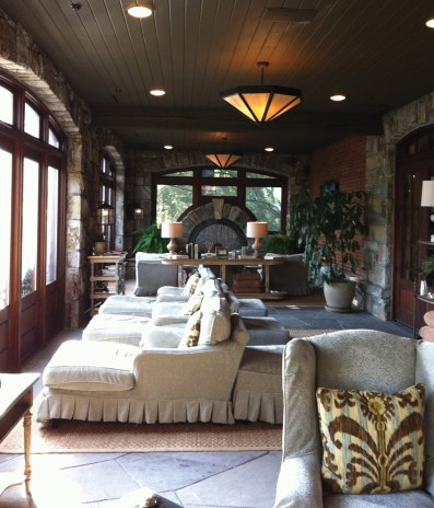 """On the spa terrace in the """"quiet room,"""" guests can relax with a cup of tea or lemon water between spa treatments. The massive fireplace burns huge logs in the winter for an added touch of coziness. The Spa Terrace offers panoramic views of downtown Highlands and the mountains beyond."""