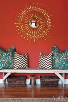 """A gold medallion mirror was one of the duo""""s many flea market finds, while baskets under the bench house """"clutterables."""""""