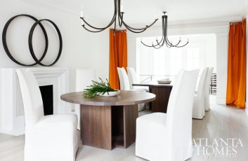The homeowners, says Douglass, were open to a less traditional take on the dining room, so she opted for two graphic tables—one round and one square—which are surrounded by South of Market's armless Jules dining chairs and anchored by a pair of identical iron chandeliers. Orange silk-and-cotton panels add dimension to the space, while round wooden bands (possibly from a barrel) add graphic interest to the space above the fireplace.