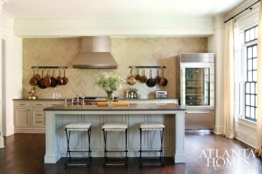 In the spirit of scaling back, tableware and sundries are stowed in lower cabinets only, allowing the limestone herringbone backsplash to take center stage. The island countertops are Lagos Azul limestone.