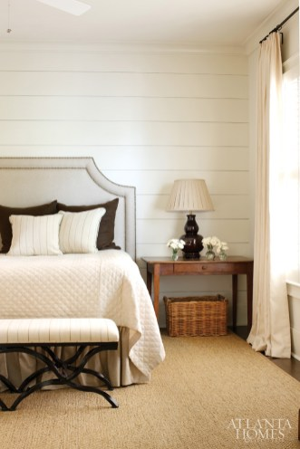 The master bedroom features a paneled accent wall, a Legacy Home coverlet in a quilted diamond texture, gourd lamps from Joseph Konrad Antiques and a bench custom-made by Iron Studio.