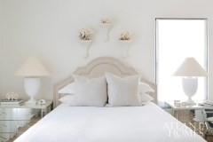 A trio of brackets holding coral specimens hangs over a bed made with crisp white linens. Mirrored chests flanking the bed contribute to the light and bright feel.