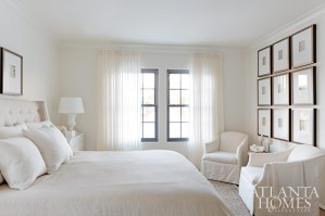 A sisal rug, sheer drapery panels and a tufted linen headboard add warmth to the clean, white master bedroom.