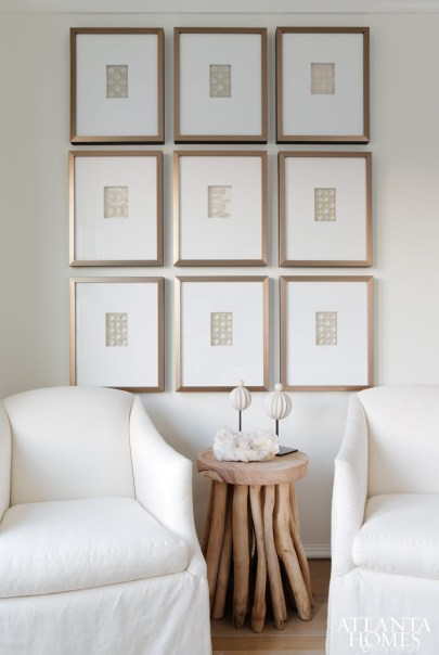 A grouping of framed crystals from Soicher Marin hang above a driftwood side table and a pair of slipcovered chairs.