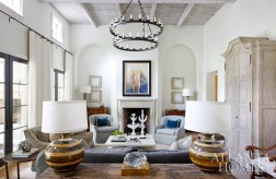 The light-filled living room spills out onto the pool loggia. The twin chandeliers and lime-washed armoire are by Formations at Jerry Pair, the table lamps are from Parc Monceau and the artwork above the fireplace is by Kyle Schwartz.