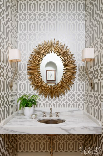Imperial Trellis wallpaper from Schumacher canvases the powder room walls. A starburst mirror from Bungalow Classic and Circa Lighting sconces above the Calcutta gold marble countertop complete the jewel box feel.