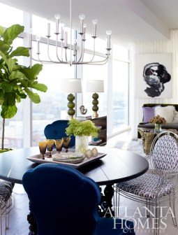 """Flanking the custom walnut dining table are pairs of graphic Opera Chairs by Casamidy and teal Arden Court Chairs by Lillian August. A large silver pebbled plate with a bevy of earthy accessories sits beneath Arteriors"""" Breck chandelier."""