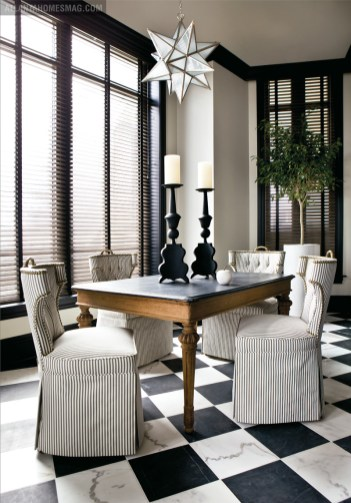 """A simple, unassuming breakfast table is surrounded by chairs upholstered in a sturdy indoor/outdoor material. Given the natural light flooding the room, Oetgen used wooden Venetian blinds at the windows """"to calm it down and not make it so fancy."""""""