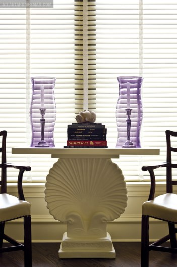Just outside the bedroom, a quiet sitting spot is softly illuminated by a pair of purple glass hurricanes.