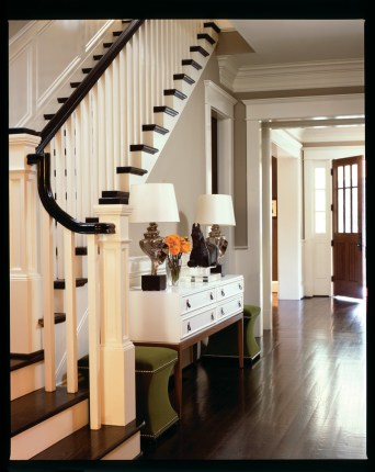 """This home""""s foyer is also its central hall, connecting the front door to the back; a sleek console""""flanked by a pair of bright green velvet ottomans""""grounds the space squarely in the middle."""
