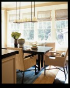 """Because the breakfast area is open to the family room, Watford carried over the same muted palette. """"I used the same contrasting linen fabrics on the Roman shades that I used in the family room drapery, but reversed the proportion of each color used,"""" he points out. A dark wood table is surrounded by woven leather chairs and a custom banquette."""