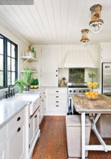 """The only thing left intact to the original kitchen were the already-gorgeous wood floors. For the rest of the design transformation, Stanton called upon the expertise of Atlanta designer Jamie McPherson, of Hearth & Home Interiors, who helped select elements such as a strong iron window, Viking appliances and the wood paneling spanning the walls. Stanton added rustic submarine lights as unexpected ceiling fixtures, their crackly patina playing up the room""""s other rich textures. """"We""""ve got the super-fancy kitchen, but we don't cook,"""" Stanton laughs. """"We tell people it makes the best Digiornos!"""" An antique hutch, at right, stores kitchen essentials."""