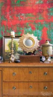 An 1860s bronze altar candlestick and a 19th-century painting are a few treasures that grace the top of a circa 1830 Biedermeier chest in Chovan Designs and Loftin Antiques.
