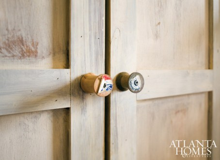 """Discarded thread spools serve as the home's """"hardware."""" Throughout the home, wood paneling is swathed in a light lime wash—the same that would have been used before the advent of latex- or oil-based paints."""