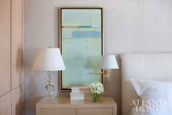 An encaustic painting by Dusty Griffith hangs atop the bedroom's upholstered walls that are covered in a Nancy Corzine fabric. The Mrs. MacDougall crystal balustrade lamp and Hinson swing-arm lamp are both available through Donghia. Bed and side table, J. Robert Scott. Floral design by Michal Evans.