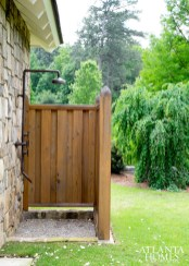 An outdoor shower is discreetly located behind a pool pavilion.