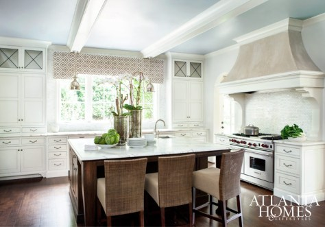 Honed Calcutta marble, a walnut island, a stucco hood and leaded glass cabinet fronts punctuate the bright and airy kitchen. Pendants from Circa Lighting.