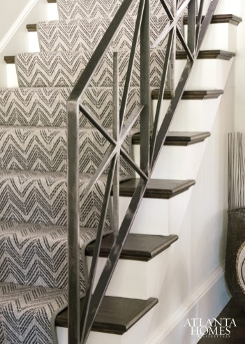 A graphic runner by Stark Carpets complements the iron stair rail custom-designed by Watford.