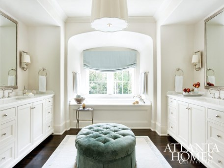 In the bright master bath, a pair of custom mirrors by Myott Studio and dual vanities frame a beautiful built-in tub niche. Chandelier, Circa Lighting. Rug, Moattar, Ltd.