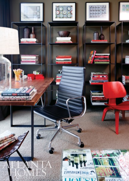The study features the Forge Dining Table with a walnut top that Westbrook transformed into an office desk. Seating from the showroom includes an Eames leather desk chair and a petite Eames molded plywood lounge chair, both by Herman Miller.