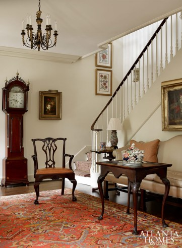 A tall case clock and Queen Anne tea table balance the sweeping staircase; the ornate chandelier is from Edgar Reeves.