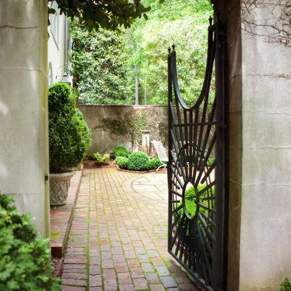 An intricate gate opens to an outdoor sitting area, where an iron bench and lush greenery reveal an idyllic retreat.