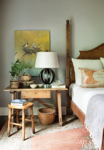To create a cozy feel in the master bedroom, Westbrook covered the walls in a muted putty color. A rustic pine table from from Robuck & Co. rests beside a pine bed. Artwork, Jeff Faust at Pryor Fine Art.