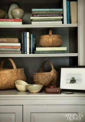 Stacks of books, pottery and woven baskets personalize this bookshelf.
