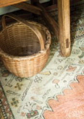 An antique Oushak from Sullivan Fine Rugs and a woven basket sit beneath a pine table in the master bedroom.