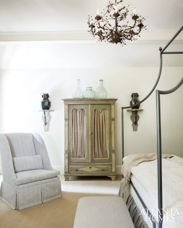 The pair of rustic vessels flanks a chicken-wire wardrobe Williams outfitted with a voluminous curtain, adding softness to an oft-used storage piece.