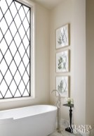 The master bath is a study in dark and light contrasts; mullion windows afford plenty of natural light.