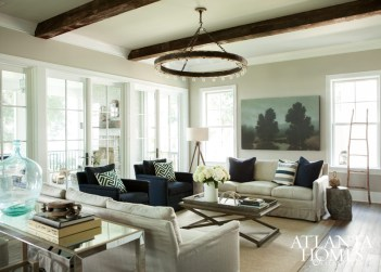 An expanse of windows creates a light and bright look in the great room, which features reclaimed wood beams and other earthy elements. Painting by Elizabeth Chapman for dk Gallery. Chandelier and floor lamp, Circa Lighting. All other furnishings, M Home & Garden.