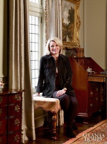 Interior designer Liza Bryan perches upon a William and Mary bench in the formal living room.
