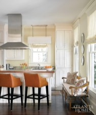 The kitchen is as high-style as it is warm and welcoming thanks to Lee barstools covered in a vivid Kravet vinyl, an antique bench and decorative plates Roman shades by Schumacher. Runner from Designer Carpets.