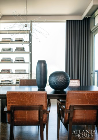 Brown leather dining chairs from Holly Hunt are embossed with an alligator print. The table suits the owner's every need; it can extend to accommodate friends and family, and serves as a desk surface, too. The chandelier is by artist Christopher Moulder.