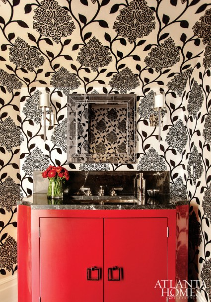 In the angular powder room, Westbrook punctuated an overscale Manuel Canovas wallcovering with a marble-topped red-lacquer vanity. The mirror is custom and the sink, faucet and sconces are by Waterworks.