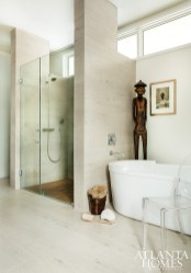 Raised windows allow for light and privacy in the spa-style master bathroom, where porcelain tile and quartz carve out a luxurious space that includes a Duravit soaking tub and a shower that's outfitted with tile colored to mimic teak. The plumbing fixtures are by Hansgrohe.