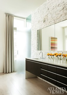The rock wall in the master bathroom showcases a different texture and hue from the stone used in the rest of the house.