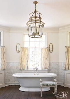 The master bathroom features a freestanding soaking tub and white marble tiles from Renaissance Tile & Bath. The mercury glass sconces and lantern are by Niermann Weeks, available through Grizzel & Mann. The polished nickel hardware is by Houles, through Ernest Gaspard & Associates. The drapery fabric is by Lee Jofa.