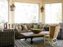 The screened-in porch is a favorite gathering spot, and a charming Orkney chair provides pint-sized seating. The sofa and club chairs are by Walters Wicker. The custom striped rug is from Eve & Staron.