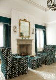 """Perched around the master bedroom's fireplace are armchairs and an ottoman upholstered in Schumacher's """"Imperial Trellis"""" velvet in Peacock. The designers chose the chairs for their scale and clean lines, which play off the curves of the tray ceiling. The gilt mirror and Currey & Company sconces were purchased by the home's former owners."""