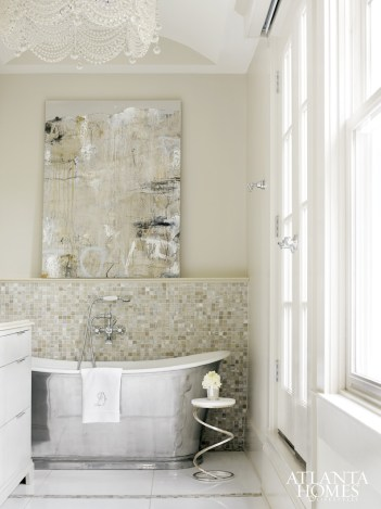 A freestanding nickel tub, a sparkling chandelier hung from an arch-top ceiling and showstopping art from Anne Irwin Fine Art fashion a glamorous but serene master bath, pictured and opposite. Plumbing fixtures by Waterworks. Crystal sconces from Brighton Collection. Spiral base table by Christopher Norma. Cabinetry by Karpaty Cabinetry and Griffith Construction.