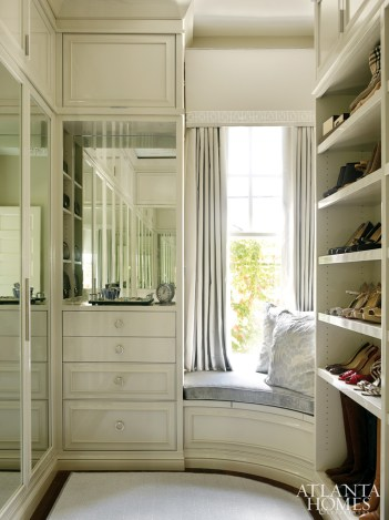The boutique-inspired master closet for her is concealed behind mirrored doors and lacquered cabinetry by Karpaty Cabinetry and Griffith Construction. Draperies and trim by Fret Fabrics. Rug by Eve and Staron. Window seat, Lee Jofa.