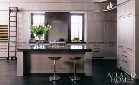 """With the idea that the kitchen feels industrial to some degree, we used a Cambria color called Wellington that felt the most 'earthy,'"" says architect and interior designer Joel Kelly of the countertop and range hood material. While the hood appears to be carved out of one piece, each leg is made from four three-centimeter pieces of material fused together. Adds Michael Bell of Bell Kitchen & Bath Studios: ""Cambria quartz allows you to get an even flow of color without using a pattern that's too dominant. There's a lot visual interest in the material."""