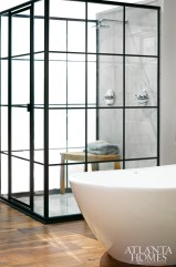 "Modeled after vintage factory windows, the shower's glass-and-aluminum enclosure was fabricated by Atlanta Glass & Mirror, Inc. ""The custom shower came to life from a sketch drawn on an iPad,"" says designer Dylan Gilliam of Home ReBuilders. ""What makes this bath truly remarkable is that there are so few items straight from stock."""