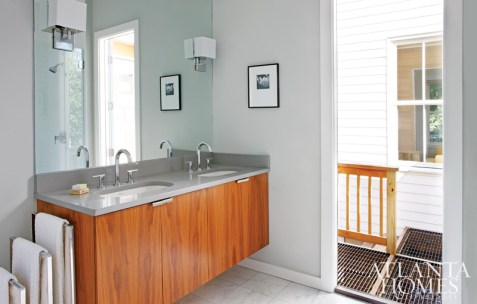 """The master bathroom is a clean-lined combination of warm-toned walnut and Georgia marble, much like the materials Wilburn used during her own era, among them pine, oak, cypress, granite and marble. """"To me, she was so far ahead of her time,"""" Carpenter says of the early 20th-century architect. A bathroom door leads to a jaunty outdoor shower."""